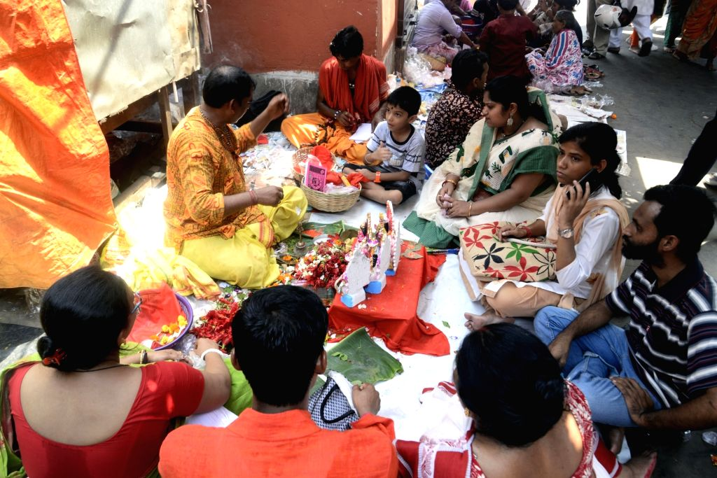 Devotees surround a priest performing rituals during Bengali New Year celebrations in Kolkata, on April 15, 2019.