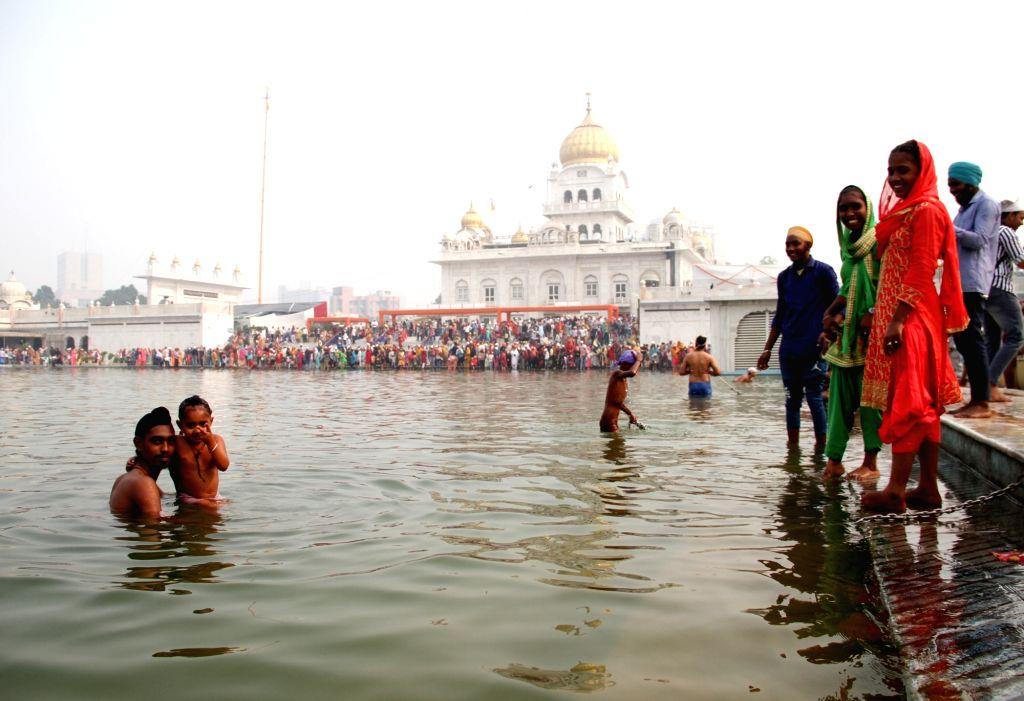 Devotees take a dip in the holy pond of Sri Bangla Sahib Gurudwara during the 550th birth anniversary celebrations of Guru Nanak Dev, in New Delhi on Nov 12, 2019. - Nanak Dev