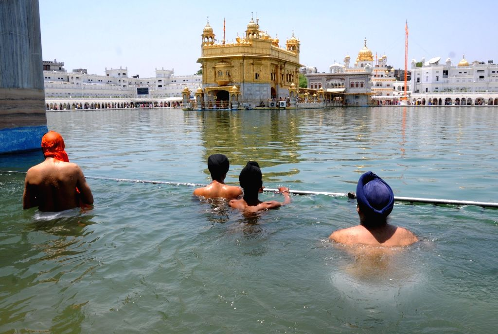 Devotees take a dip in the holy pond on the martyrdom day of Guru Arjan Dev at the Golden Temple in Amritsar, on June 7, 2019. - Arjan Dev