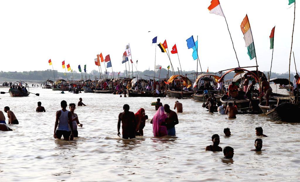 Devotees take a holy dip at Sangam on the occasion of Guru Purnima, in Prayagraj on July 16, 2019.