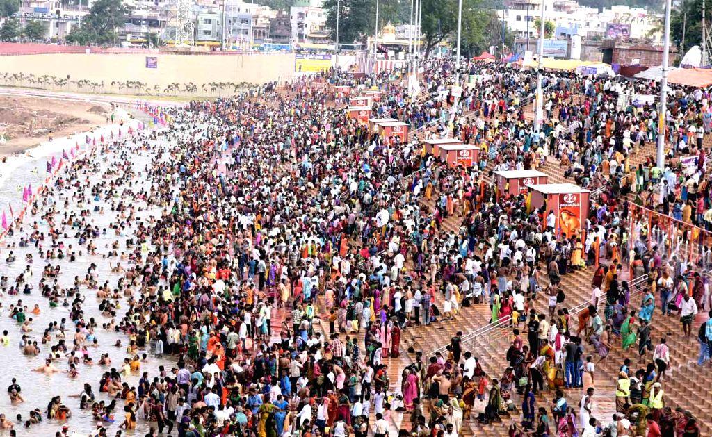 Devotees take a holy dip in the Krishna river during Krishna Pushkaralu at Durga ghat in Vijayawada on Aug 22, 2016.