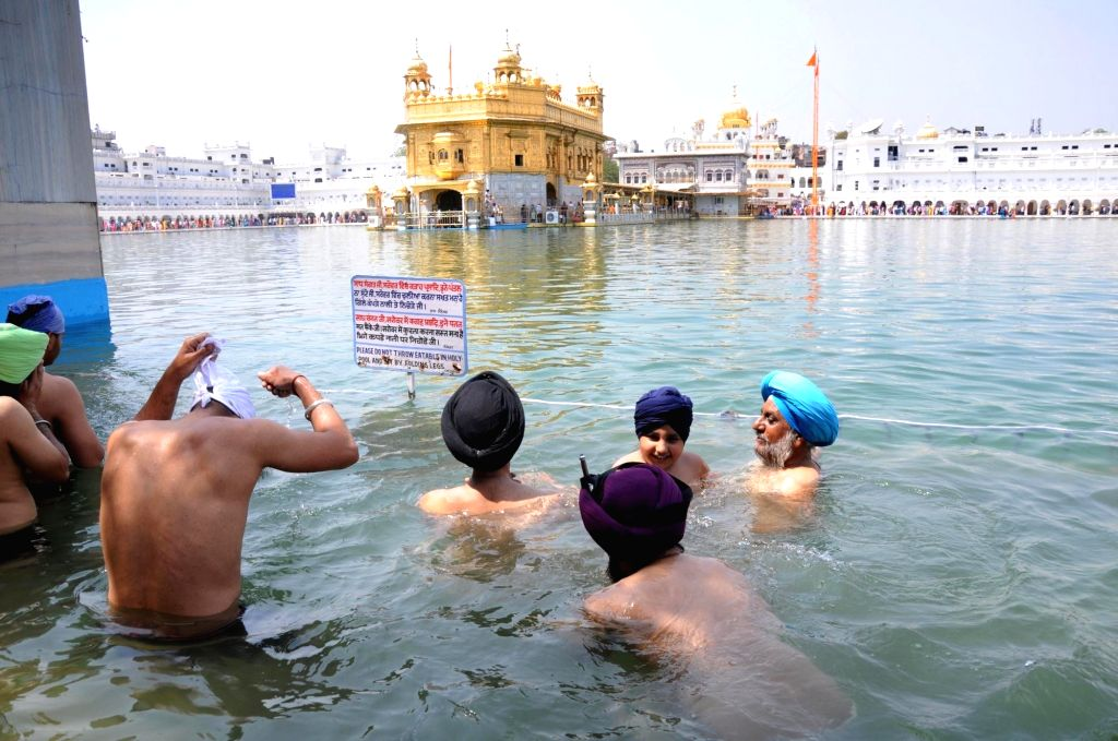 Devotees take a holy dip in the pond at Golden Temple on the occasion of the birth anniversary of fifth Sikh master Sri Guru Arjan Dev Ji, in Amritsar on April 7, 2018.