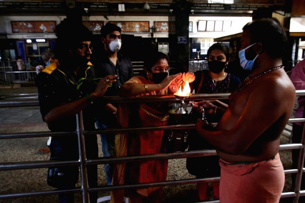 Devotees take aarti blessing from a distance at a temple that reopened after the Tamil Nadu Government permitted the reopening of the places of worship as part of several relaxations that ...