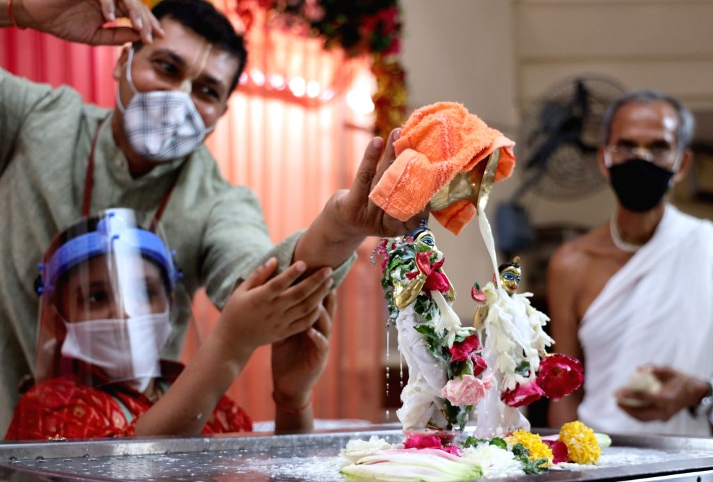 Devotees wash the idol of Lord Krishna with milk during Krishna Janmashtami celebrations at the ISKCON Temple in New Delhi on Aug 12, 2020.