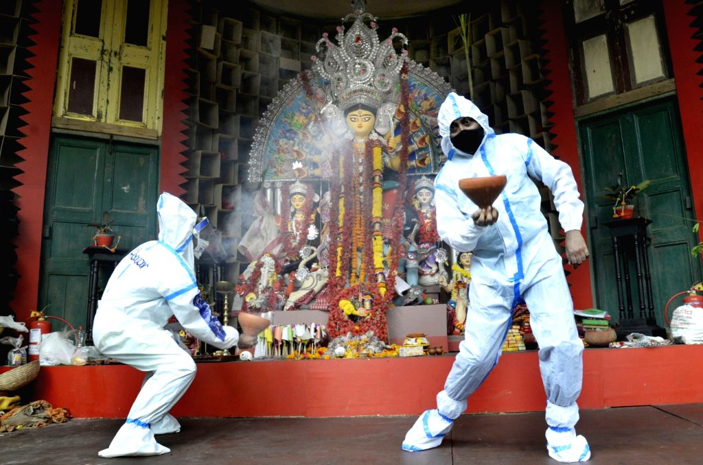 Devotees wearing Personal Protective Equipment (PPE) kits perform Dhunuchi dance - a devotional dance form performed holding a dhunuchi, which contains the burning coconut husk with dhuno ...