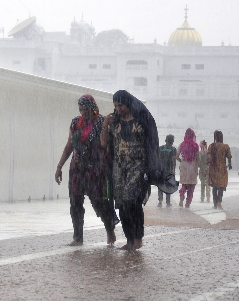 Devotes runs for shelter at the Golden temple as rains lash Amritsar on June 27, 2017.