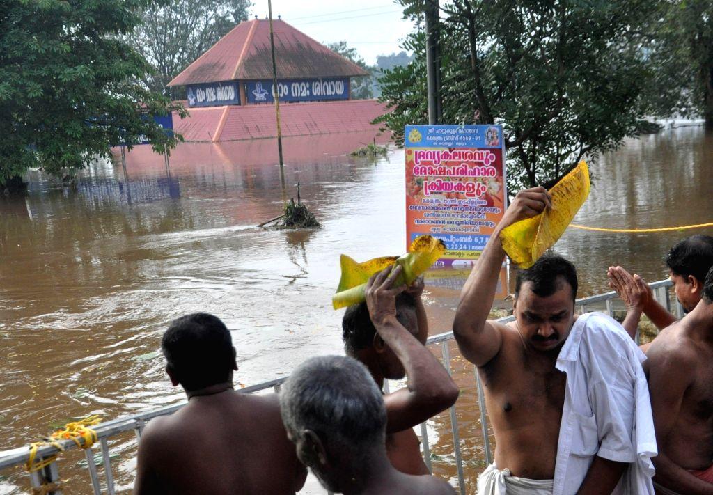 Devottees doing Balitharpan at the bank of Periyar near Aluva Mahadeva temple in Kochi on the eve of Karkataka Vavu on Aug 11, 2018. Heavy rain and flood water surrounding the Aluva Siva ...
