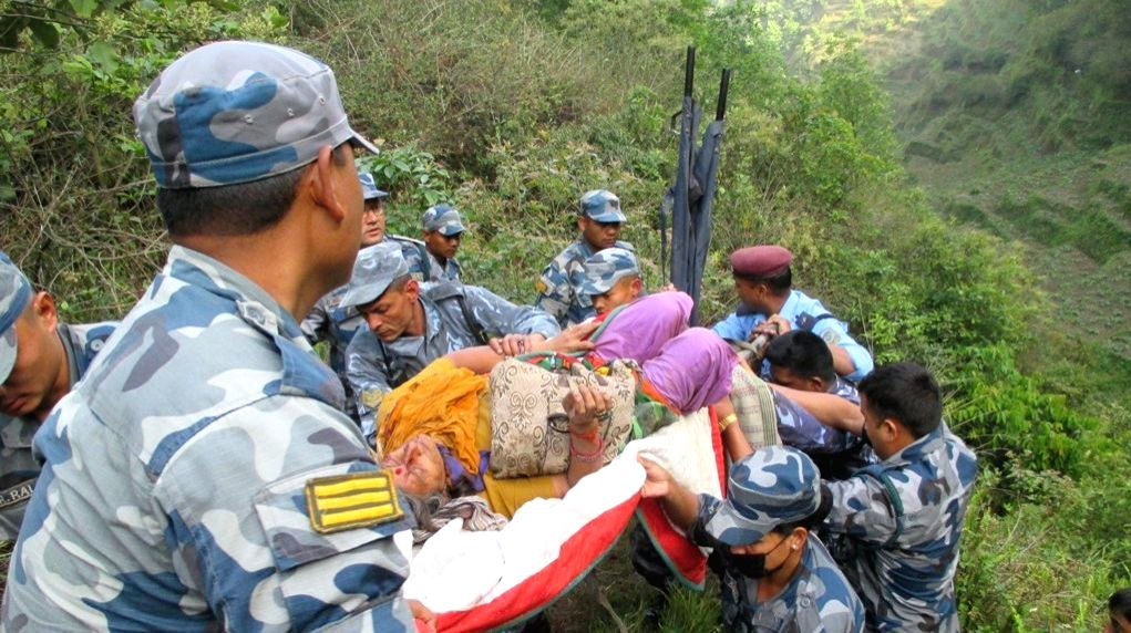 Nepalese security personnel transfer a victim of a bus accident in Dhading District, some 50 km west of Kathmandu, Nepal, April 22, 2015. Twelve Indian pilgrims ...
