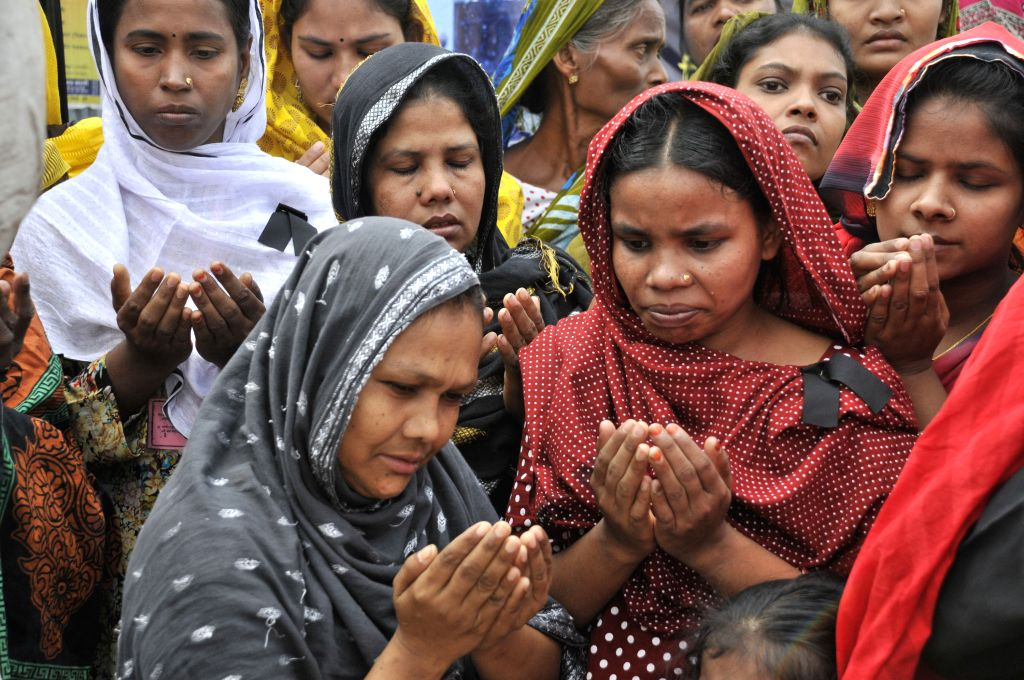 Relatives of victims pray at the site of Rana Plaza building collapse during a commemoration in Savar, on the outskirts of Dhaka, Bangladesh, April 24, 2014. ...