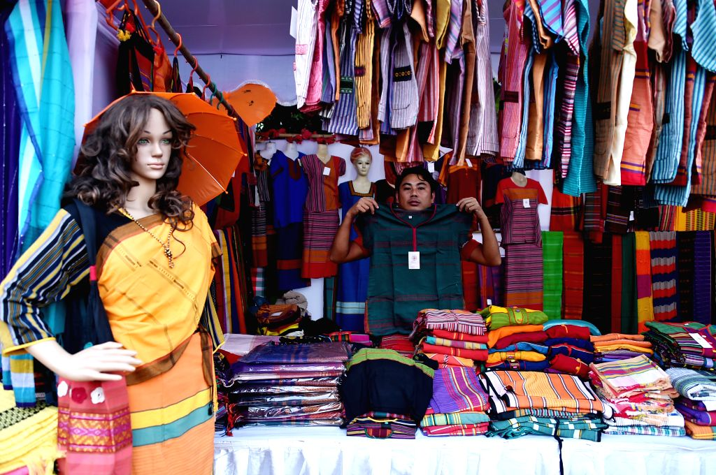 DHAKA, Dec. 6, 2019 - A man shows clothes at his booth during a fair promoting indigenous cultures and products in Dhaka, Bangladesh on Dec. 5, 2019.