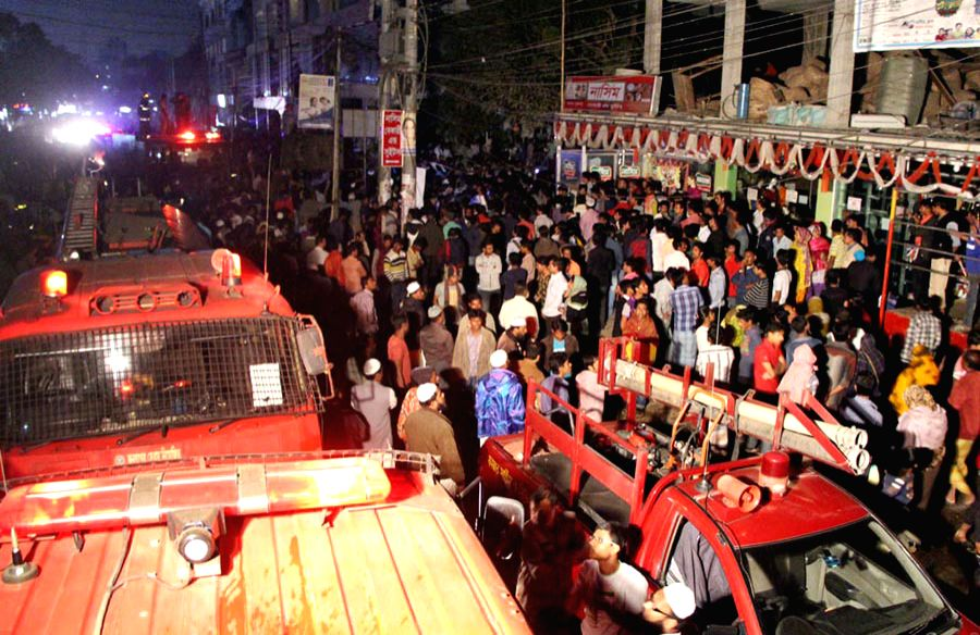 Local people gather near the fire site of a plastic factory in Dhaka, Bangladesh, Jan. 31, 2015. A major fire engulfed a plastic packaging factory in Dhaka's downtown .
