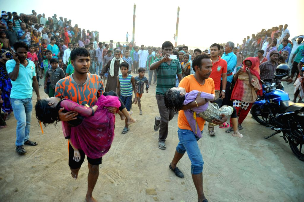 Rescuers carry bodies of victims after a ferry accident on the Padma River in Manikganj district, Bangladesh, Feb. 22, 2015. Death toll in Bangladesh's ferry accident ...