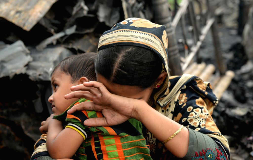 A woman reacts after a fire accident at Agargon in Dhaka, Bangladesh, Feb. 25, 2015. A six-year-old child was killed and about 50 shanties were destroyed in the ...