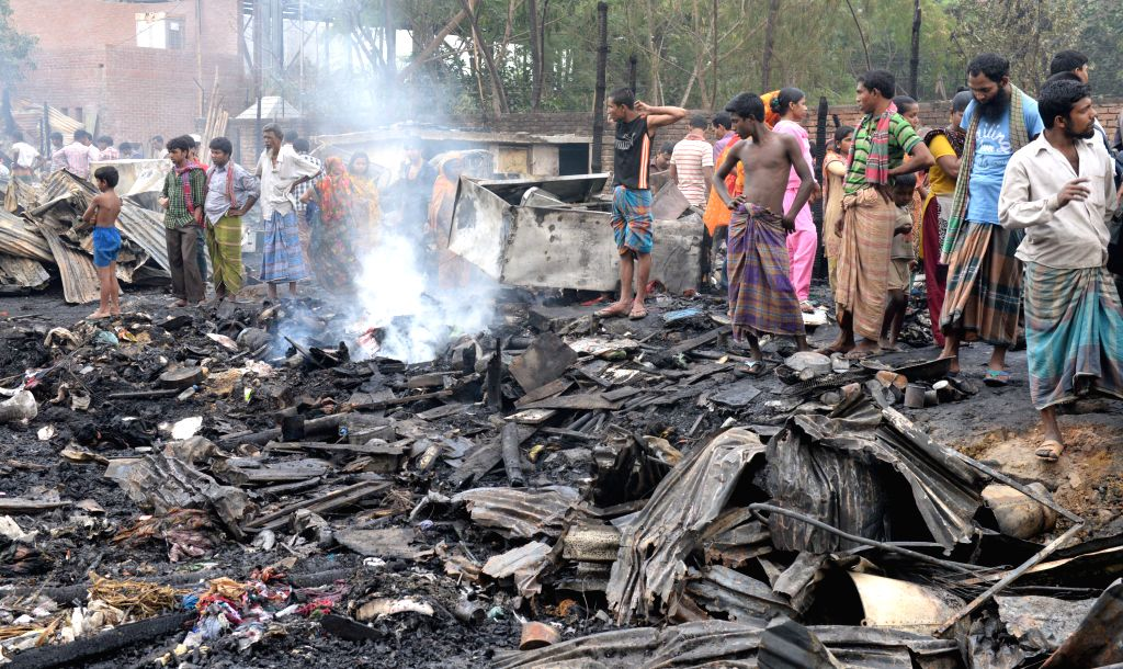 Bangladeshi slum dwellers search for their belongings after a fire accident at Agargon in Dhaka, Bangladesh, Feb. 25, 2015. A six-year-old child was killed and about ...