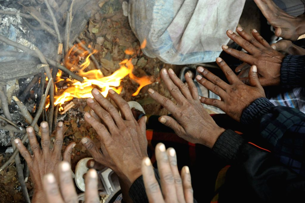 City dwellers make fire to warm themselves in winter morning in Dhaka, Bangladesh, Jan. 19, 2015. A cold wave has been sweeping through various parts of Bangladesh ...