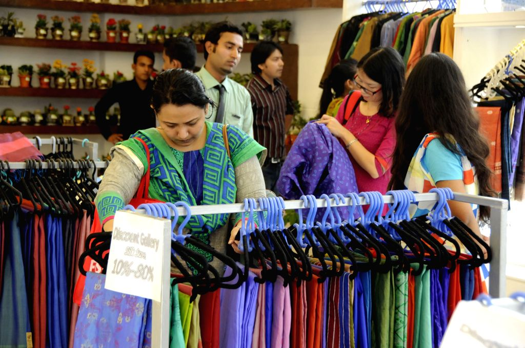 Bangladeshi people choose cloth at a stall during the Dhaka International Trade Fair in Dhaka, Bangladesh, Jan. 4, 2015. The Dhaka International Trade Fair held in ...