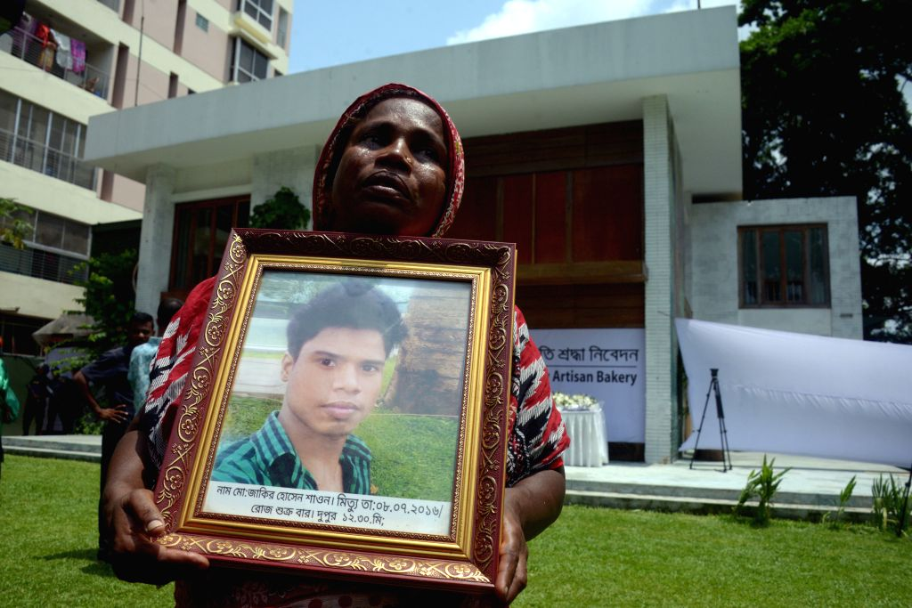 DHAKA, July 1, 2018 (Xinhua) -- Mother of a victim in Holey Artisan Bakery attack holds a portrait of her son during a memorial event marking the second anniversary of the attack in Dhaka, Bangladesh on July 1, 2018. Twenty people were hacked to deat
