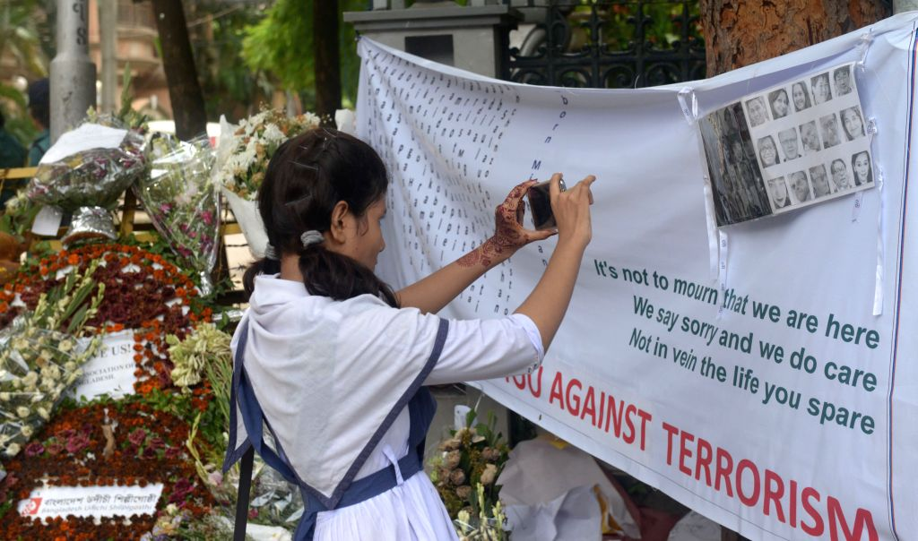 DHAKA, July 10, 2016 - A school girl takes video near the Spanish restaurant where the militant attack took place in Dhaka, Bangladesh, July 10, 2016. After a video where three Bangla-speaking men ...