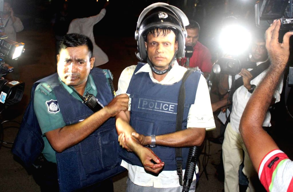 DHAKA, July 2, 2016 - An injured policeman is escorted away by his colleague after an attack in Dhaka, Bangladesh, July 2, 2016. Gunmen have shot dead two police officials, police said, in the first ...