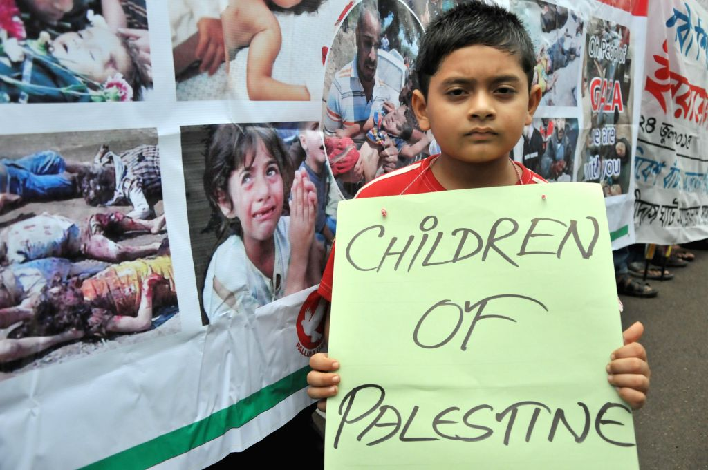 A Bangladeshi child holds a placard during a protest against ongoing Israeli air raids on the Gaza Strip in Dhaka, Bangladesh, July 24, 2014. Israeli offensive in the