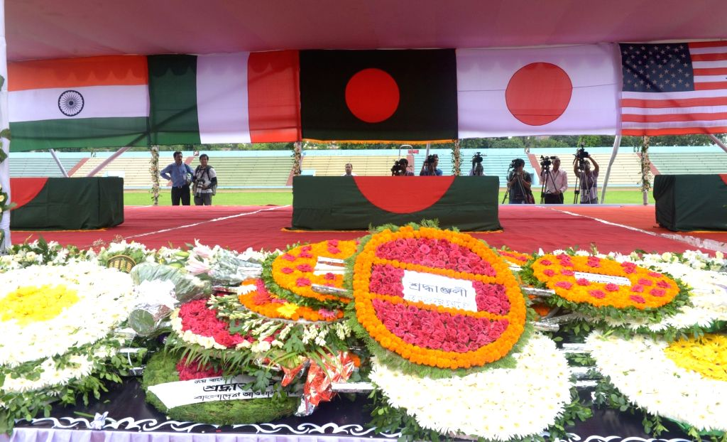 DHAKA, July 4, 2016 - Photo taken on July 4, 2016 shows flowers laid in front of coffins during a memorial service for those killed in a bloody siege at the Army Stadium in Dhaka, Bangladesh, July 4, ...