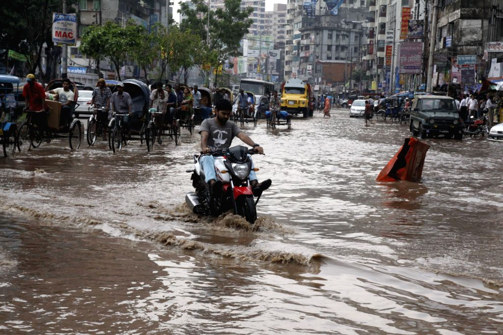A man rides a motorbike through the flood waters after a heavy downpour in Dhaka, Bangladesh, June 17, 2014.