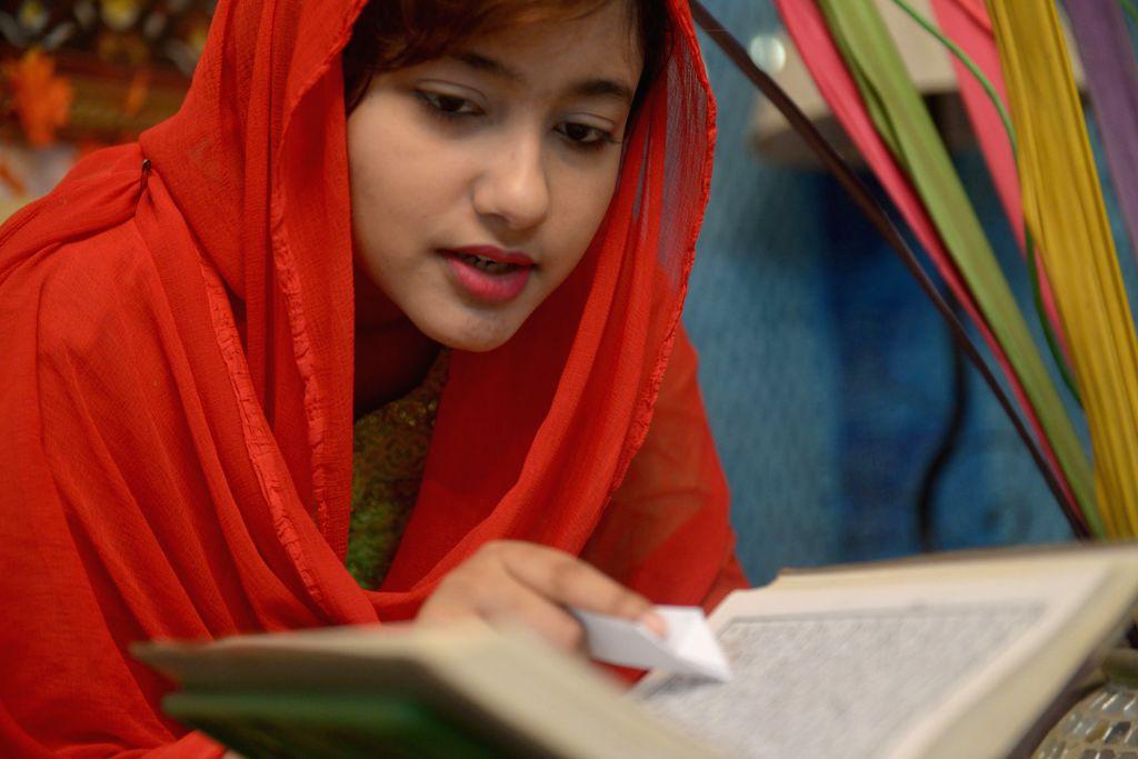 DHAKA, June 27, 2016 - A young girl recites the Quran during the Islamic holy month of Ramadan in Dhaka, Bangladesh, June 27, 2016.
