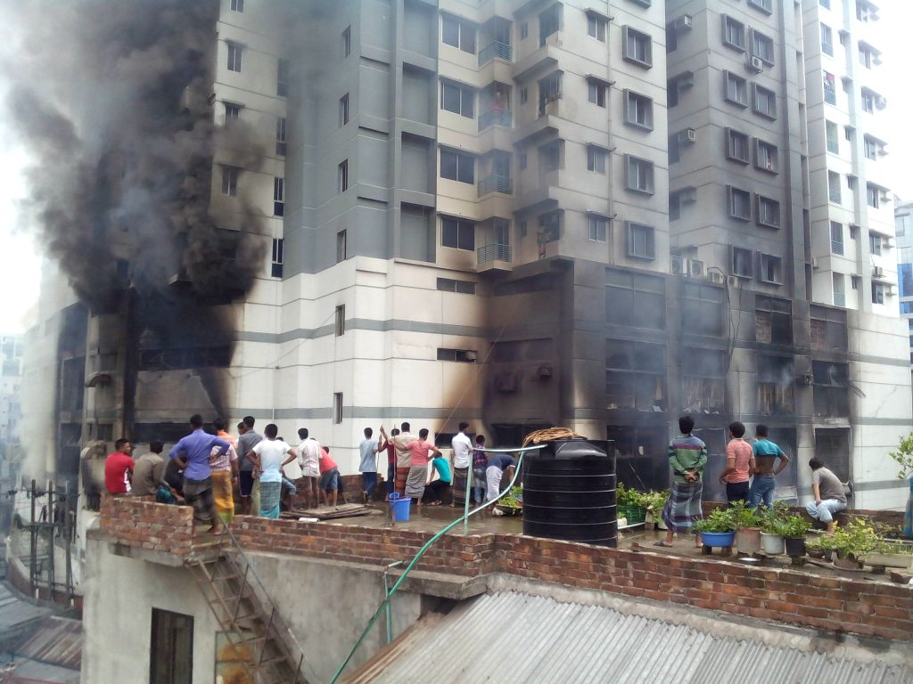 DHAKA, June 29, 2016 - People watch heavy smoke from a fire at a residential multi-story building at Uttar Badda in Dhaka, Bangladesh, June 29, 2016.