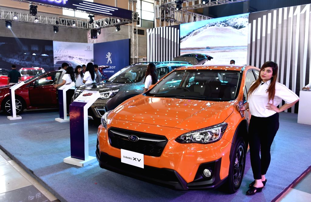 DHAKA, March 14, 2019 - A model poses beside a car at a motor show in Dhaka, capital of Bangladesh, on March 14, 2019. Bangladesh's biggest international automotive exhibition kicked off in capital ...