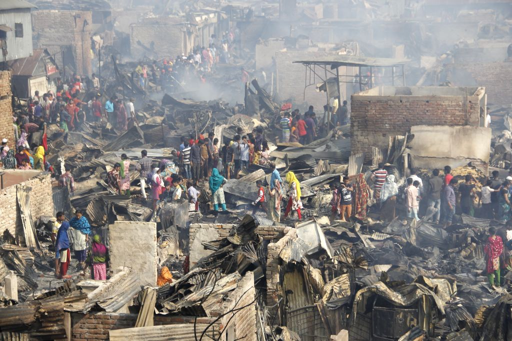 DHAKA, March 16, 2017 - Photo taken on March 16, 2017 shows slum dwellers searching for valuable things after devastating fire destroyed their shanties in Dhaka, capital of Bangladesh. A devastating ...