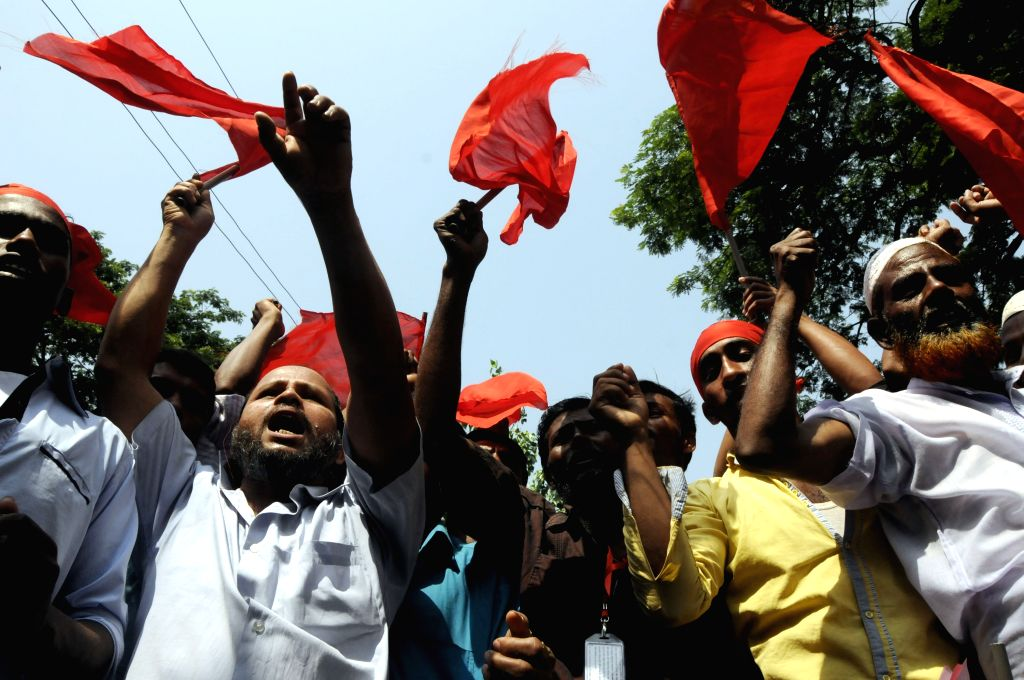 Bangladeshi garment workers shout slogans during a march marking the International Labor Day in Dhaka, Bangladesh, May 1, 2015.