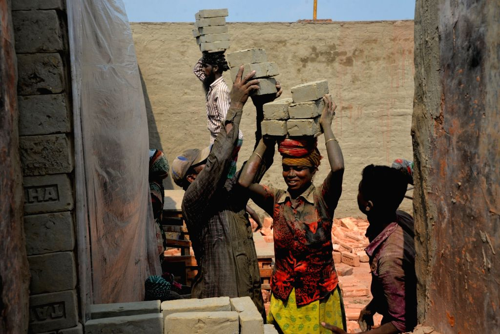 DHAKA, Nov. 4, 2018 - A female laborer carries bricks on her head at a brick plant at Amin Bazar on the outskirts of Dhaka, Bangladesh, on Nov. 4, 2018.