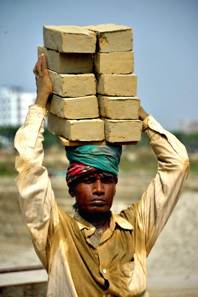 DHAKA, Nov. 4, 2018 - A laborer carries bricks on his head at a brick plant at Amin Bazar on the outskirts of Dhaka, Bangladesh, on Nov. 4, 2018.