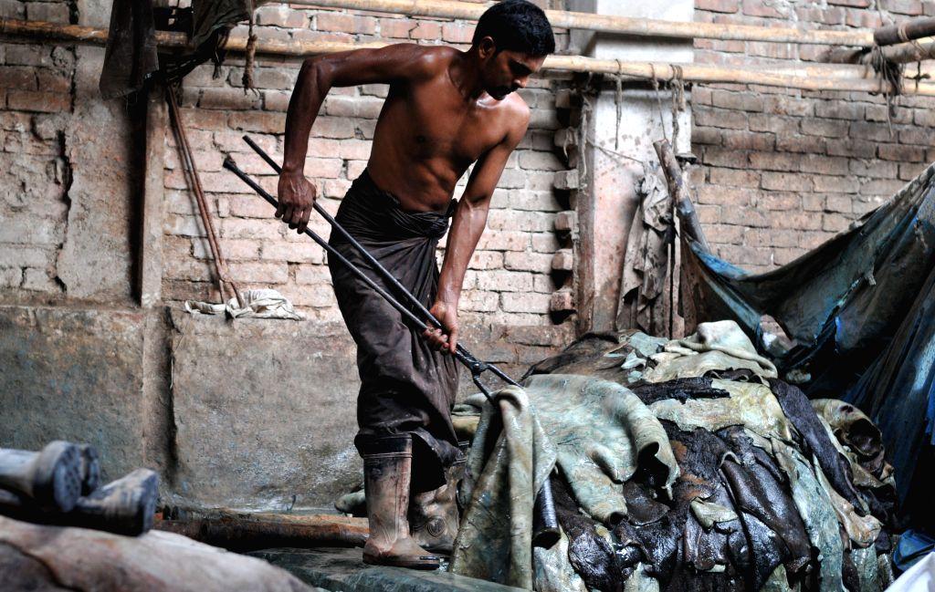 DHAKA, Oct. 13, 2014 (Xinhua) -- A man works in a leather factory after the Eid-ul-Adha festival in Dhaka, Bangladesh, Oct. 13, 2014. (Photo: Xinhua/Shariful Islam/IANS)