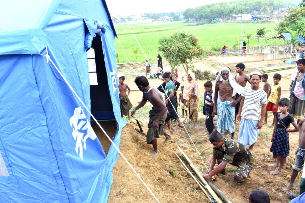 DHAKA, Oct. 4, 2017 - An Army personnel helps a Rohingya family to set up Chinese relief tent at a camp in Cox's Bazaar district, Bangladesh, on Oct. 3, 2017. China has sent relief supplies for ...