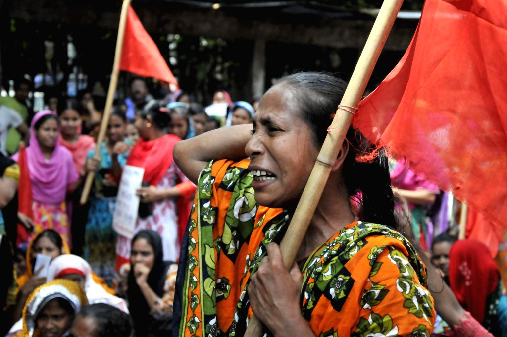 A woman shouts slogans during a protest rally in front of the National Press Club in Dhaka, Bangladesh, Sept. 7, 2014. Hundreds of garment workers demanded their ...