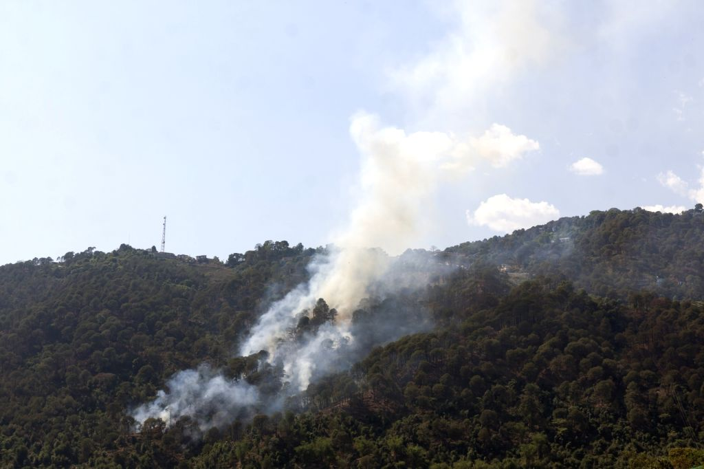 Dharamsala: Smoke billows out of a forest that caught fire as temperatures rise, near Himachal Pradesh's Dharamsala on May 29, 2019. (Photo: IANS)