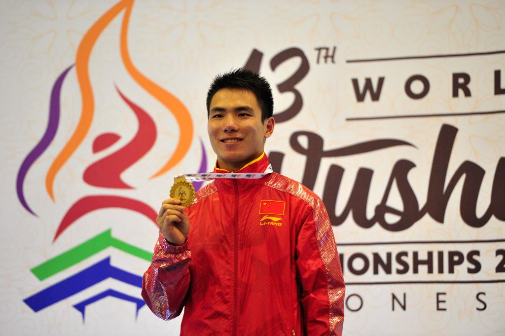 Di Wang of China poses on the podium during the awarding ceremony of Men's Nanquan at the 13th World Wushu Championship in Jakarta, Indonesia, Nov. 14, 2015. Di ...