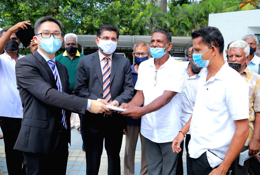 Director General of Health Services in Sri Lanka Anil Jasinghe (2nd L, Front), Charge d'affaires of the Chinese Embassy Hu Wei (1st L, Front) and local three-wheel ...