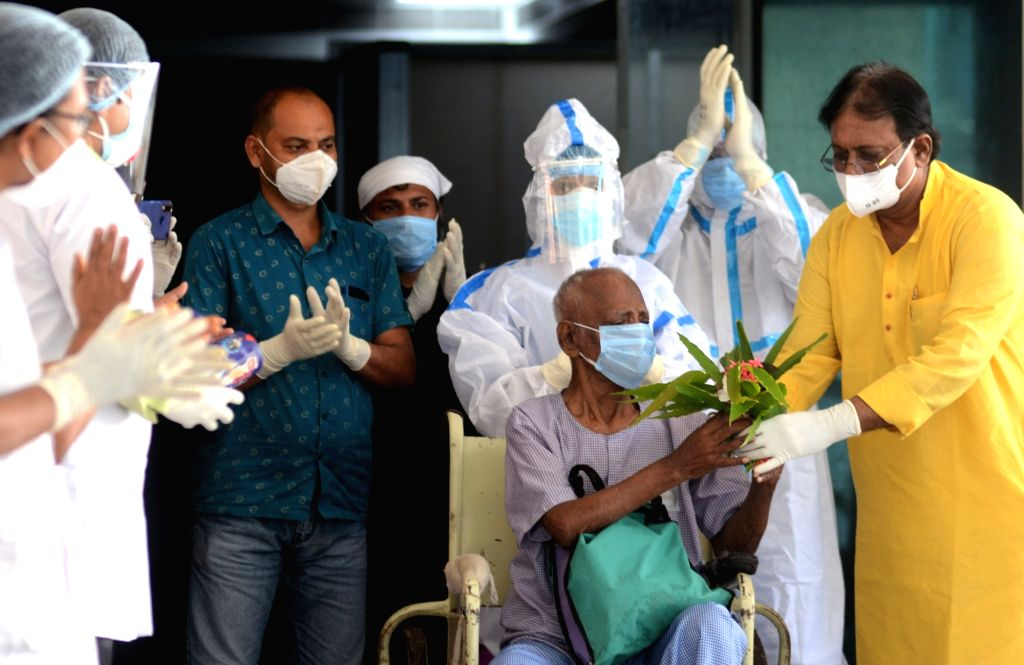 Doctors and nurses offer flowers to the 94-yr-old COVID-19 patient Lalmohon Seth, as he leaves for his home after being discharged from the Kolkata Medical College and Hospital post ... - Lalmohon Seth