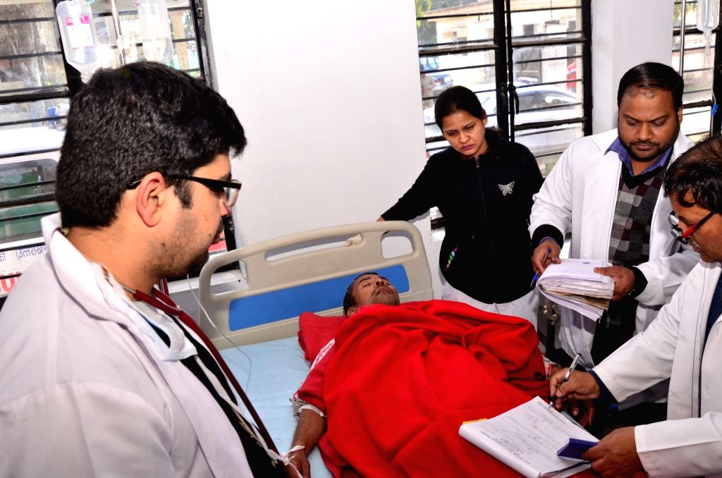 Doctors examining a patient who was admitted after consuming spurious liquor in Uttarakhand's Roorkee, on Feb 9, 2019. At least 30 people died on Friday after consuming spurious liquor in ...