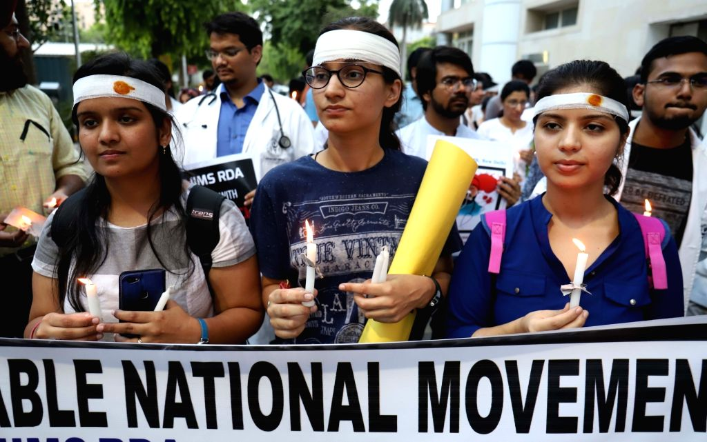 Doctors participate in a candlelight vigil to protest against the brutal attack on two junior doctors in a Kolkata Hospital, at AIIMS in New Delhi on June 14, 2019.