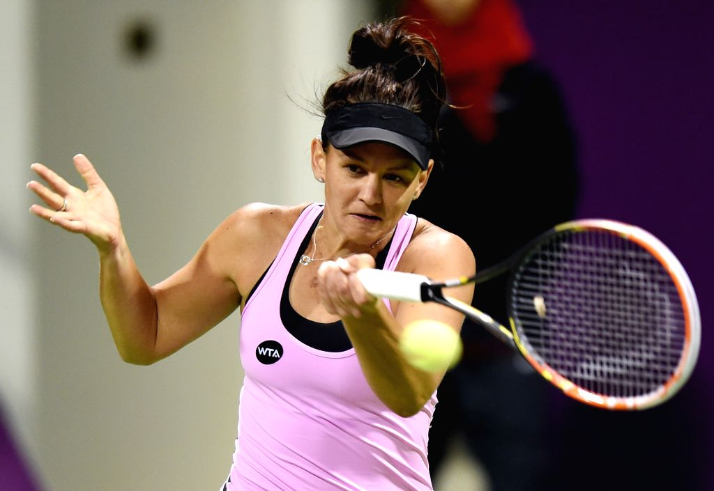 Casey Dellacqua of Australia returns the ball during the first round match against Venus Williams of the United States in the WTA Qatar Open tennis tournament in Doha, ...