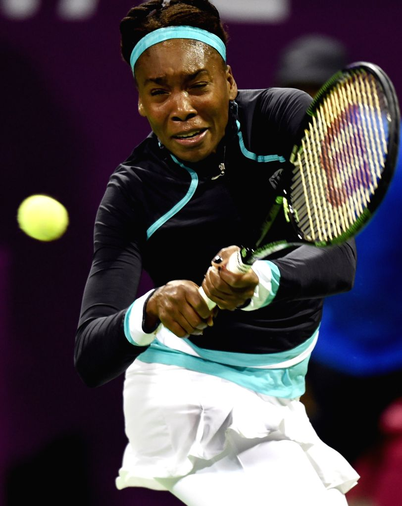 Venus Williams of the United States returns the ball during the first round match against Casey Dellacqua of Australia in the WTA Qatar Open tennis tournament in Doha, ...