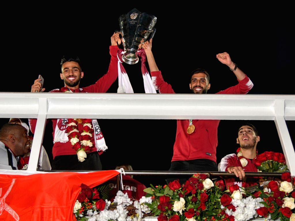 DOHA, Feb. 3, 2019 - Qatar national soccer team captain and forward Hasan Al Haydos (2nc R) holds the trophy upon arrival at Doha International Airport in Doha, Qatar on Feb. 2, 2019. Qatar won 3-1 ...