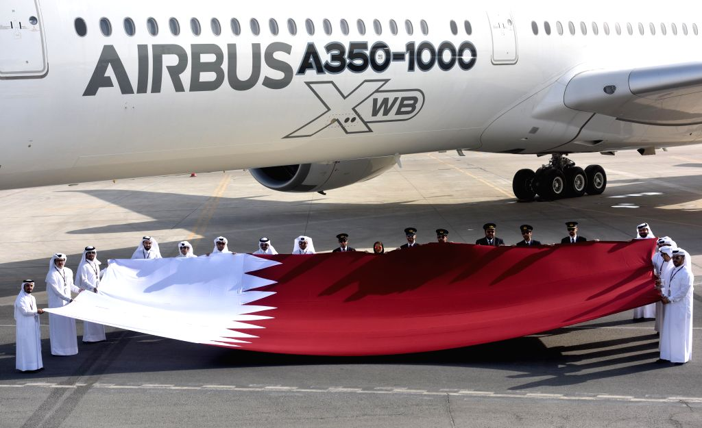 DOHA, Jan. 27, 2018 - Qatar Airways staff hold a national flag of Qatar next to an Airbus A350-1000 jet at Doha International Airport in Doha, capital of Qatar, on Jan. 27, 2018. The brand new ...