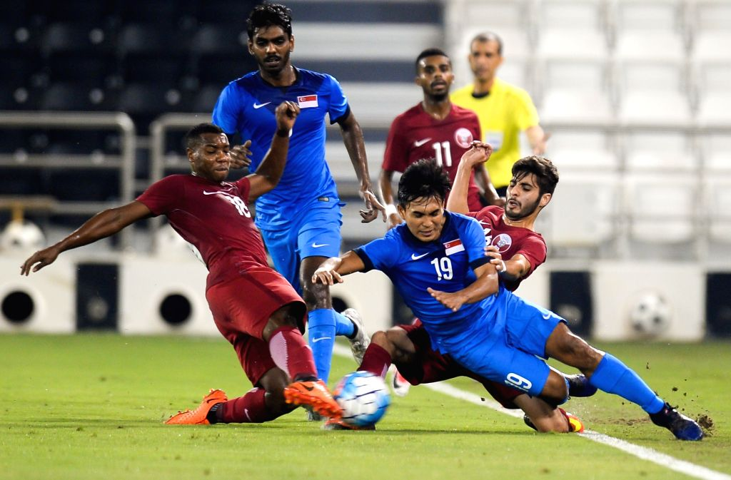 DOHA, June 16, 2017 - Salem Ali Al Hajri (front R) of Qatar fights for the ball with Joshua Bernard Pereira (front L) of Singapore during a U22 International friendly soccer match at the Jassim Bin ...