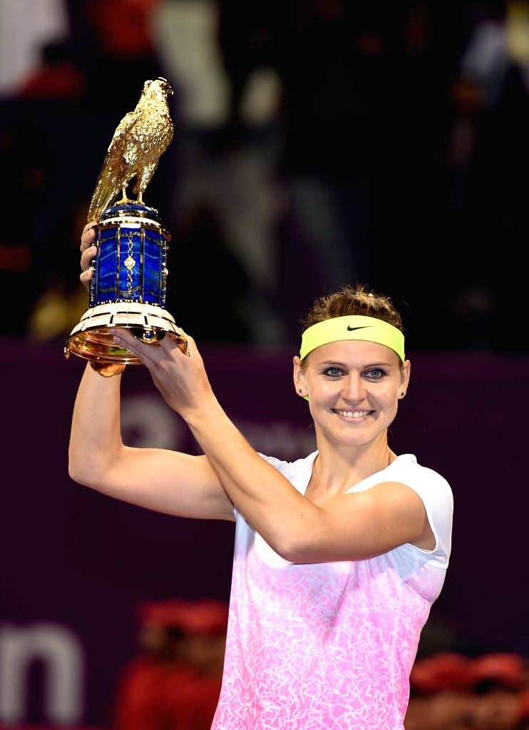 Lucie Safarova of the Czech Republic celebrates with the Qatar Open tennis tournament trophy after defeating Victoria Azarenka of Belarus in the women's singles final ...