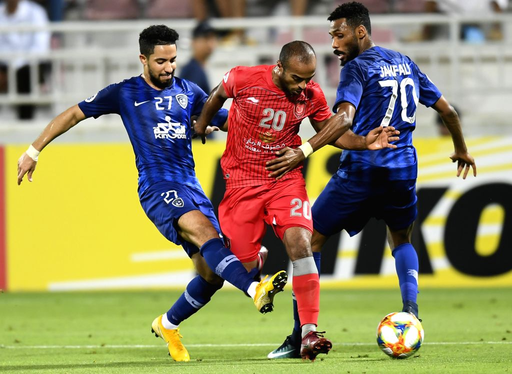 DOHA, May 21, 2019 - Hattan Bahebri (L) and Mohammed Jahfali (R) of Al Hilal vies with Ali Hassan Afif of Al Duhail during the AFC Champions League group C soccer match between Qatar's Al Duhail and ... - Hassan Afif