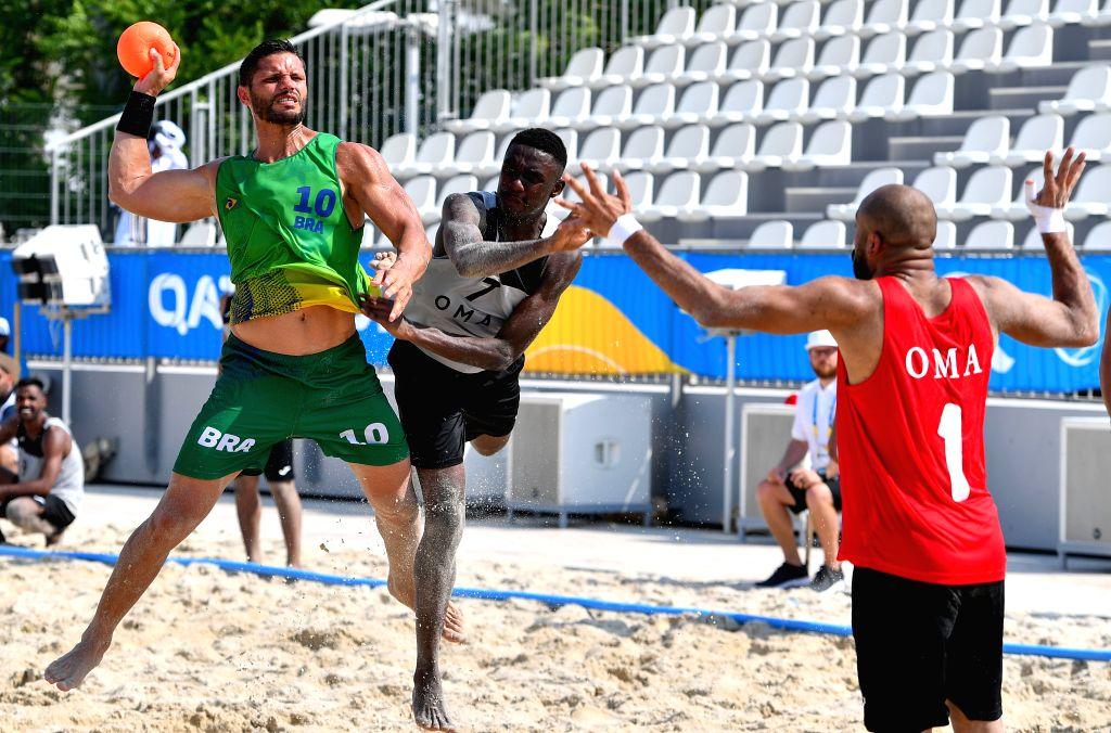 DOHA, Oct. 12, 2019 - De Paes Pires Gil Vicente (L) of Brazil vies with Al Maashari Azan (C) and Al Siyabi Hudhaifa of Oman during the men's beach handball preliminary round Group A match between ...